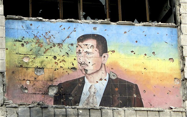 A colourful facade depicting President Assad is riddled with bullet holes.
