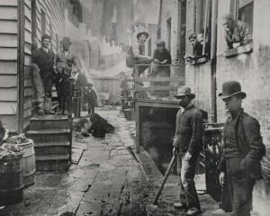 1024px-1-Riis-Bandits-Roost-New-York-City-Slum-1890