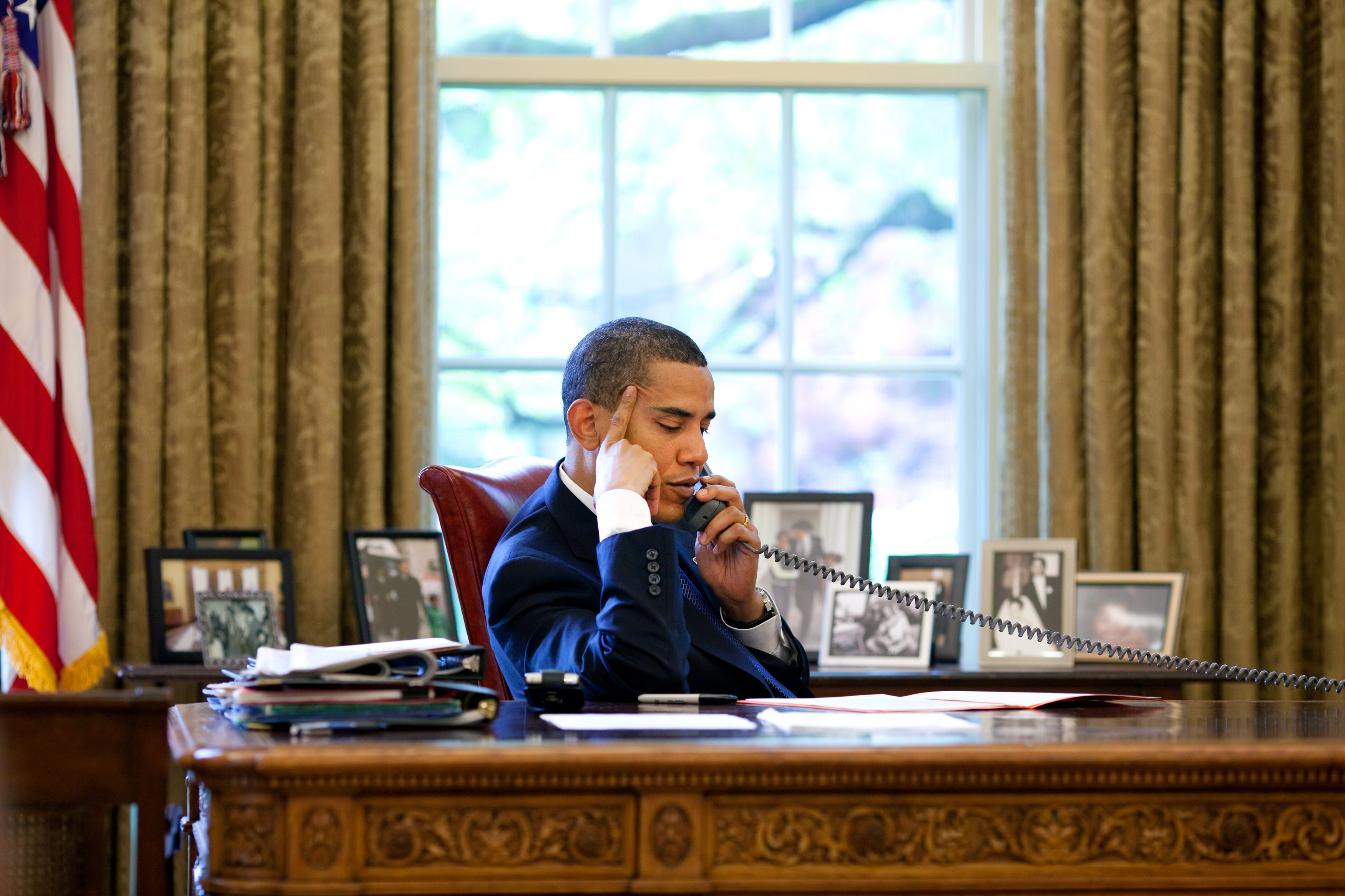 President Barack Obama sits at his desk in the  Oval Office during a phone call with Chinese President Hu Jintao May 6, 2009. Official White House Photo by Pete Souza.  This official White House photograph is being made available for publication by news organizations and/or for personal use printing by the subject(s) of the photograph. The photograph may not be manipulated in any way or used in materials, advertisements, products, or promotions that in any way suggest approval or endorsement of the President, the First Family, or the White House.
