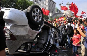 Demonstrators hold Chinese flags and banners beside an overturned car of a Japanese brand during a protest in Xi'an