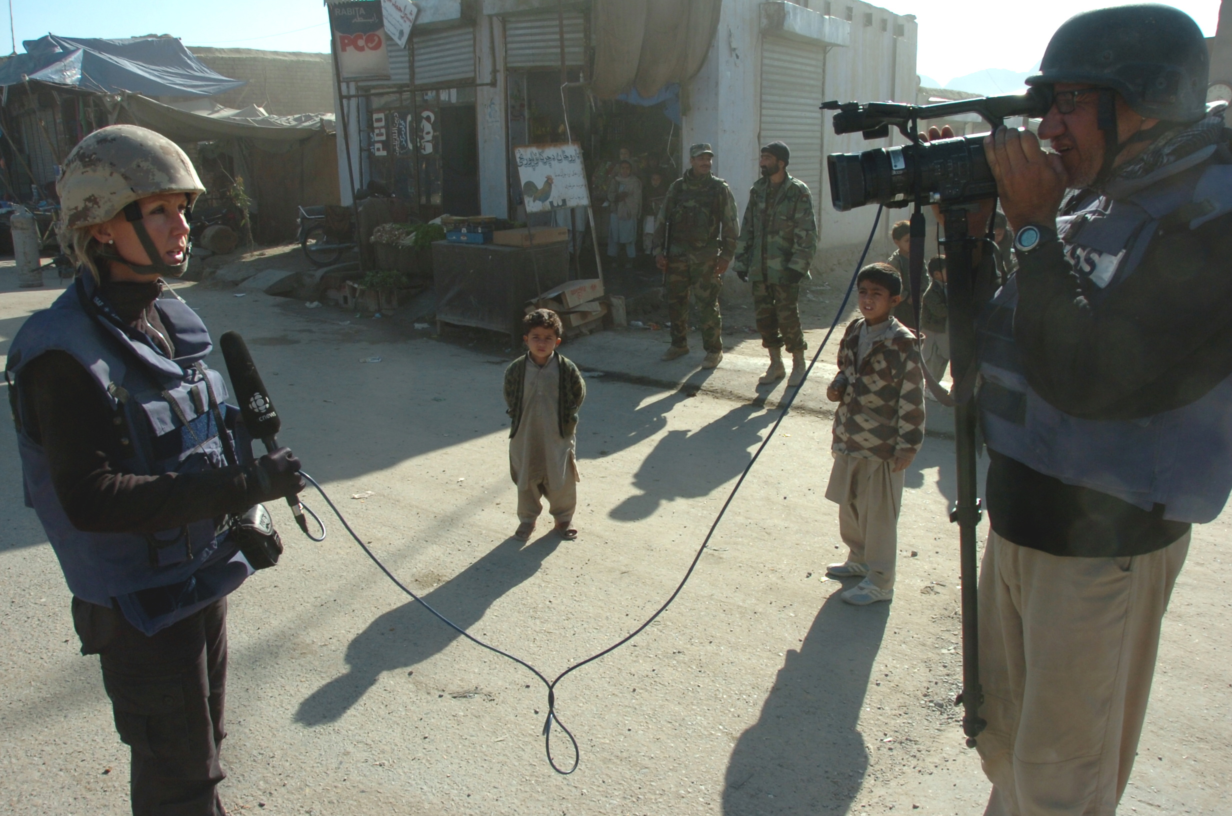 English/Anglais AR2006-S002-0048 December 19, 2006  Kandahar, Afghanistan Reporter Laurie Graham and Cameraman Al Lawrence of the Canadian Broadcasting Corporation (CBC) do an 'on camera' on the main street of Bazaar-e-Panjwaii while two local boys watch with fascination.  CBC joined a Civilian Military Cooperation (CIMIC) Patrol through the streets of Bazaar-e-Panjwaii.  The patrol originated at the gates of Forward Operating Base Ma'Sum Ghar and ended two kilometers east at an Afghan National Army Checkpoint.  Its purpose was to gauge the mood of the town and to do quick assessments of the population.  Joint Task Force Afghanistan (JTF-Afg) is Canada's contribution to NATO's International Security Assistance Force (ISAF) in Afghanistan. The focus of this mission is to help Afghans rebuild their lives, families, communities and nation.  Canadian Forces personnel in Afghanistan are working to improve the quality of life of Afghans by providing a more secure environment in which Afghan society can recover from more than 25 years of conflict. The Canadian Forces (CF) contribution in Afghanistan comprises about 2,500 soldiers, most of who serve in Kandahar province with a smaller number of personnel assigned to Kabul, various military headquarters, and civilian organizations.  Photo By:  Capt Edward Stewart JTF-AFG Op ATHENA Roto 2 1 RCR BG PAO French/Français AR2006-S002-0048 19 décembre 2006  Kandahar (Afghanistan) Le caméraman de la Société Radio-Canada (SRC), Al Lawrence, en compagnie de la journaliste Laurie Graham, filme la rue principale de Bazaar-e-Panjwaii sous le regard curieux de deux garçons du pays. Des employés de la SRC ont suivi une patrouille de coopération civilo-militaire (COCIM) dans les rues de Bazaar-e-Panjwaii. La patrouille partait des barrières de la base d'opérations avancée Ma'Sum Ghar et se rendait jusqu'à un point de contrôle de l'Armée nationale afgh