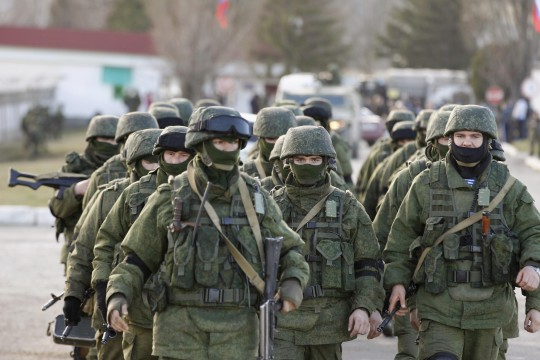 Military personnel, believed to be Russian servicemen, walk outside the territory of a Ukrainian military unit in the village of Perevalnoye outside Simferopol March 3, 2014. Ukraine mobilised for war on Sunday and Washington threatened to isolate Russia economically after President Vladimir Putin declared he had the right to invade his neighbour in Moscow's biggest confrontation with the West since the Cold War. Russian forces have already bloodlessly seized Crimea, an isolated Black Sea peninsula where Moscow has a naval base. REUTERS/Baz Ratner (UKRAINE - Tags: CIVIL UNREST MILITARY POLITICS)